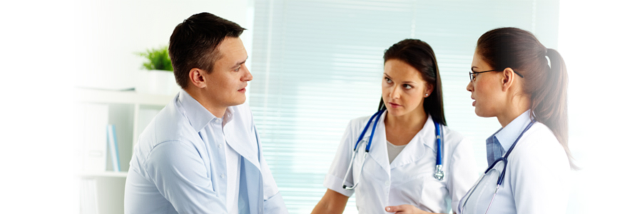Two female medical professionals speaking with male patient